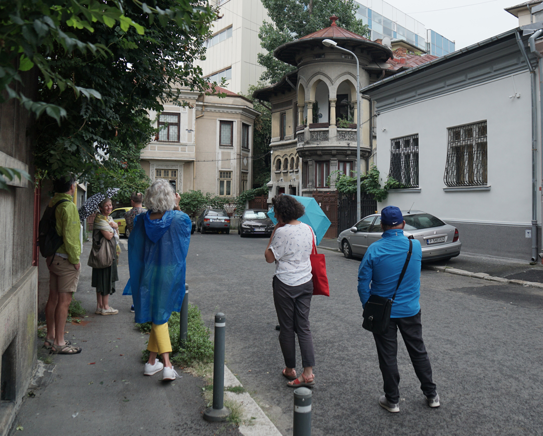 guide and group of 4 tourists on picturesque street looking at romantic looking house