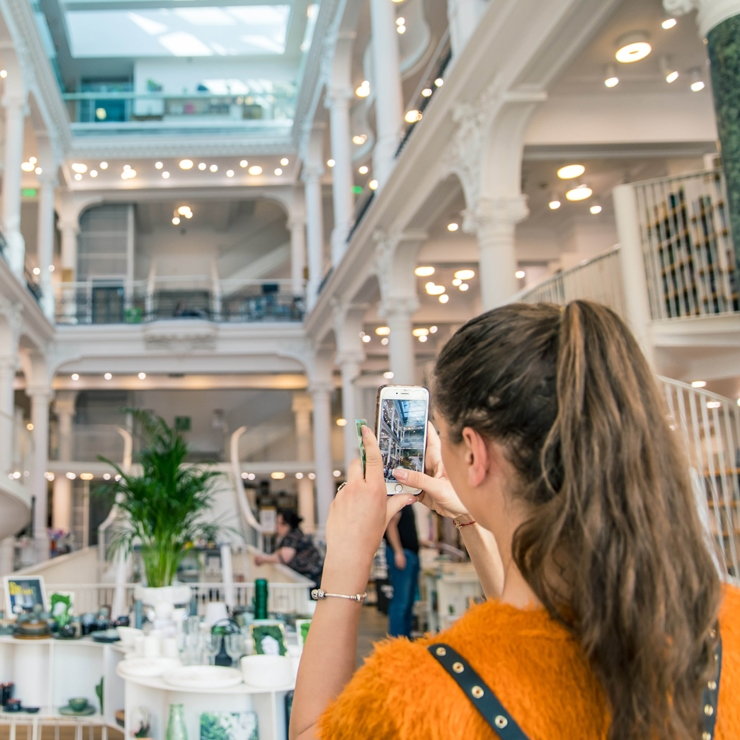 girl photographing interior of building